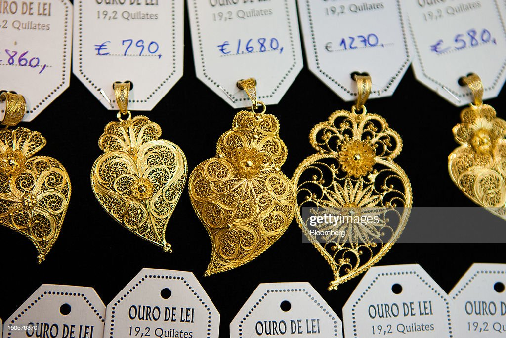 Traditional Portuguese gold jewelry sits on display beside euro price tags in the window of a jewelry store in Lisbon, Portugal, on Wednesday, Aug. 22, 2012. In Portugal, the historical home of some of Europe's biggest gold reserves, the number of jewelry stores, which include cash-for-gold shops, increased 29 percent in 2011 from a year earlier, a study commissioned by parliament found. Photographer: Mario Proenca/Bloomberg via Getty Images