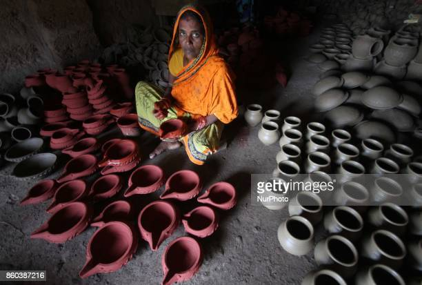 Traditional potters busy to make earthen lamps at their workshop before to supply it to the market for sale ahead of the festival of lights...