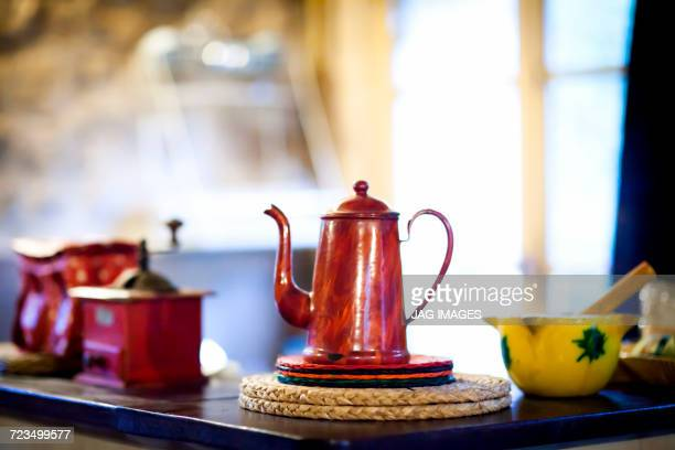 Traditional red coffee pot and coffee grinder on kitchen counter