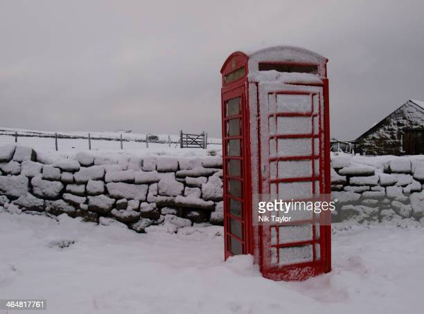 CONTENT] Traditional red telephone box next to stone wall in the snow Dartmoor Devon UK