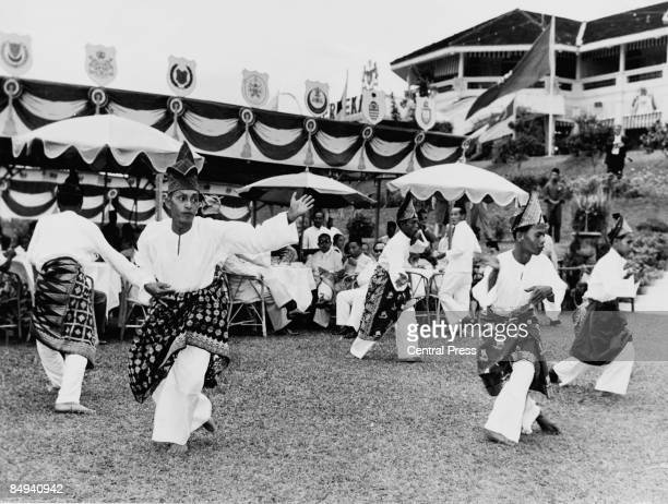 Traditional Ronggeng dancers perform for guests at a garden party during celebrations of the Federation of Malaya's independence within the...