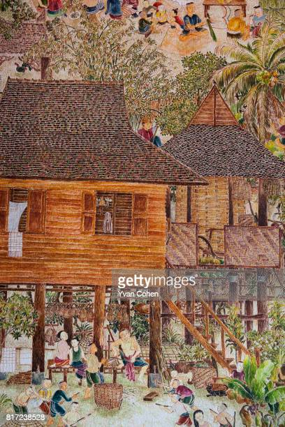 Traditional rural scenes showing wooden houses on stilts are part of a mural which adorns the walls of the Wat Pratu Pong temple in Lampang. The...