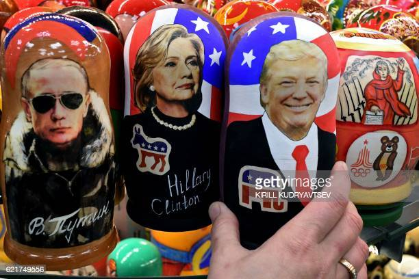 TOPSHOT Traditional Russian wooden nesting dolls Matryoshka dolls depicting Russia's President Vladimir Putin US Democratic presidential nominee...