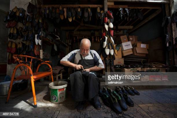 Traditional senior shoemaker making handmade leather shoes