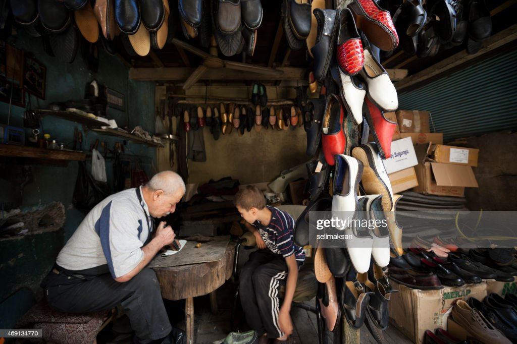 Traditional senior shoemaker teaching his apprentice how to work : Stock Photo