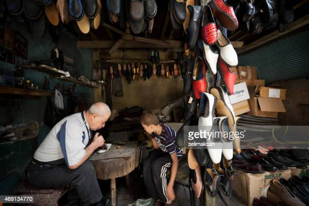 Traditional senior shoemaker teaching his apprentice how to work