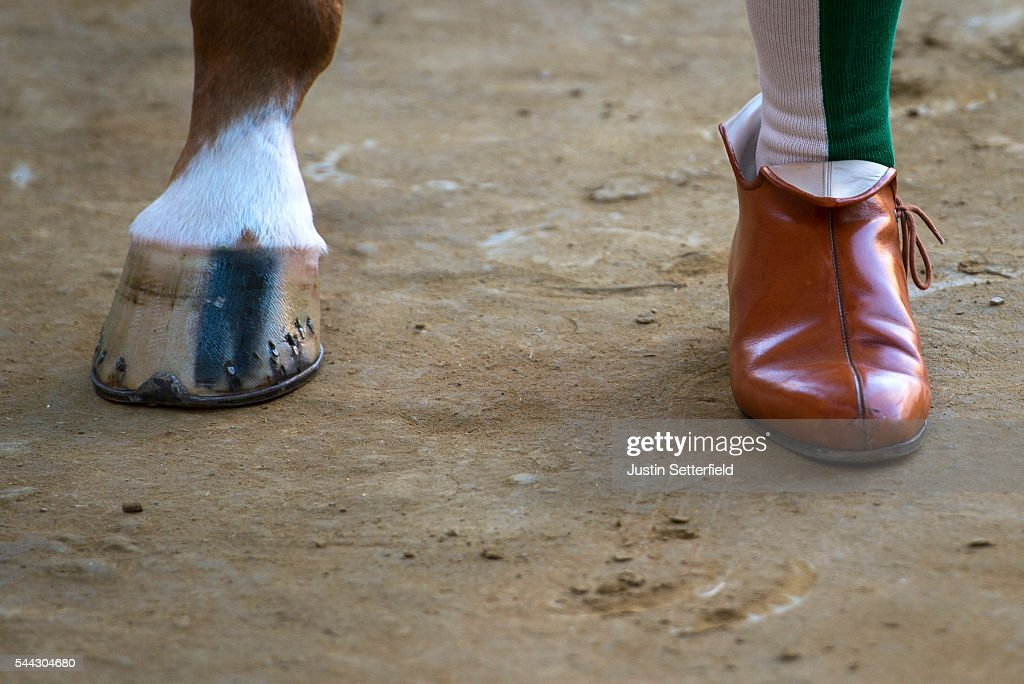 A traditional shoe and horse hoof are seen during the parade for the historical Italian horse race of the Palio Di Siena on July 02, 2016 in Siena, Italy. The Palio di Siena, known locally simply as Il Palio, is a horse race that is held twice each year on 2 July and 16 August, in Siena, Italy. Ten horses representing ten of the seventeen districts 'Contradas' with jockeys 'Fantini' riding bareback compete during a three lap race around a makeshift course built in the 'Piazza del Campo' the city's central square to win the Palio banner. The Palio di Siena is more than a simple horse race. It is the culmination of ongoing rivalry and competition between the contrade. The lead-up and the day of the race are invested with passion and pride. The Palio held on 2 July is named Palio di Provenzano, in honour of the Madonna of Provenzano, a Marian devotion particular to Siena which developed around an icon from the Terzo Camollia. The race winner is awarded a banner of painted silk, or palio, which is hand-painted by a different artist for each race.