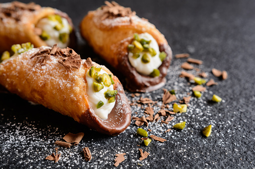 Traditional Sicilian cannoli stuffed with ricotta and pistachios 614978918
