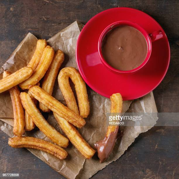 Traditional spanish treat churros with red cup of chocolate sauce served on baking paper over dark wooden background Overhead view square image