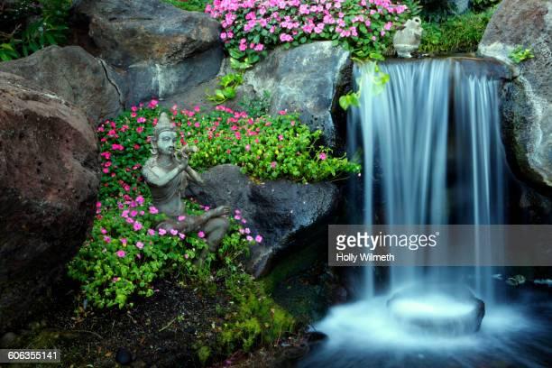 Traditional statue near waterfall