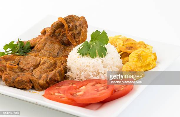 Traditional stewed lamb made and served the Cuban way with tomato tomato sauce white rice and salty banana chips