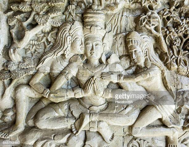 traditional stone carving of two women and man - buddha stock pictures, royalty-free photos & images