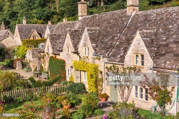 Traditional stone cottages with gardens in the Cotswold village of Bibury, Gloucestershire UK