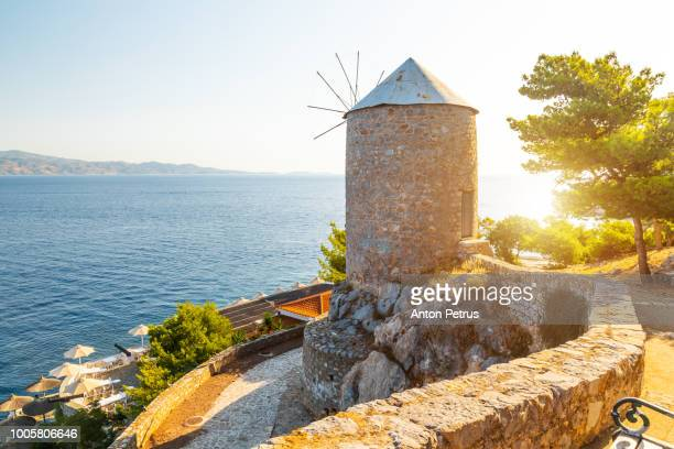 Traditional stone windmill at sunset in Hydra island, Greece
