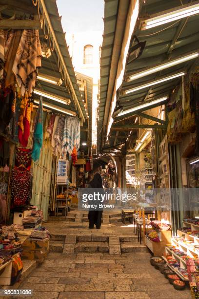 traditional street and shops with one arab woman from back in old jerusalem. - east jerusalem stock pictures, royalty-free photos & images