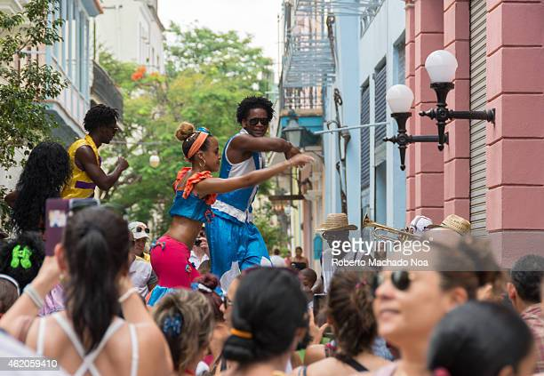 Traditional street show by people dancing on stilts happening in Old Havana while the tourist crowd looks and listen to the afro music played