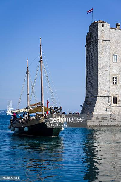 Traditional style wooden boat used for taking tourists on sightseeing cruises entering the old town harbour in Dubrovnik, Croatia.