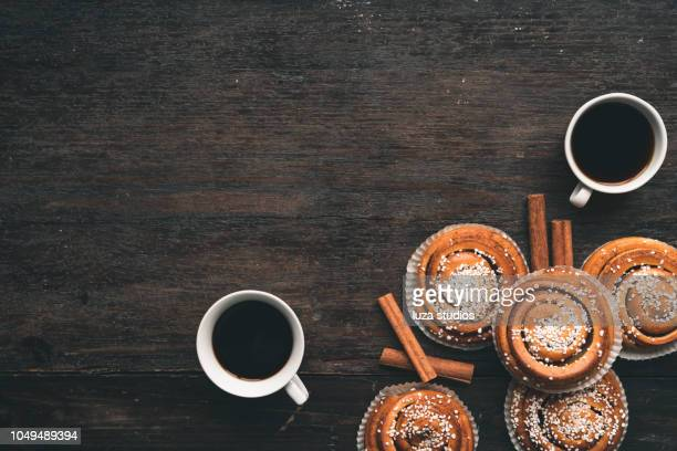 traditional swedish cinnamon bun on a wooden table - swedish culture stock pictures, royalty-free photos & images