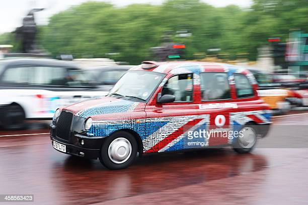 Traditional taxi in Union Jack colors speeding