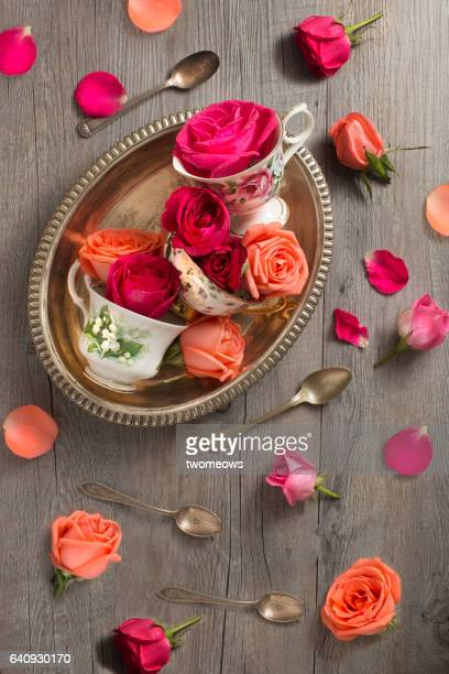 Traditional tea cups with roses on rustic wooden table top.