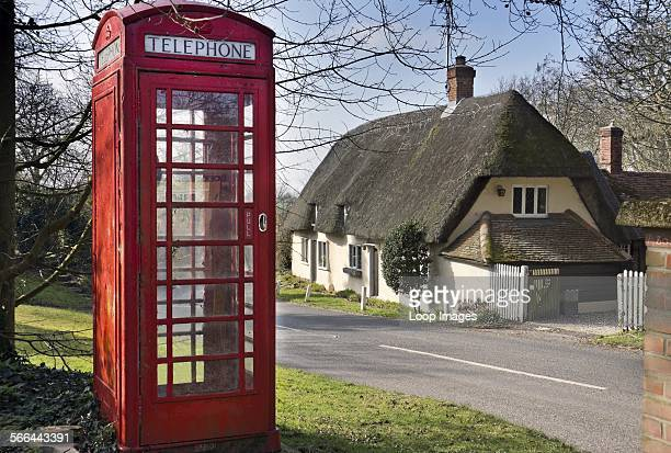 Traditional telephone box opposite a thatched cottage in the village of Brent Pelham
