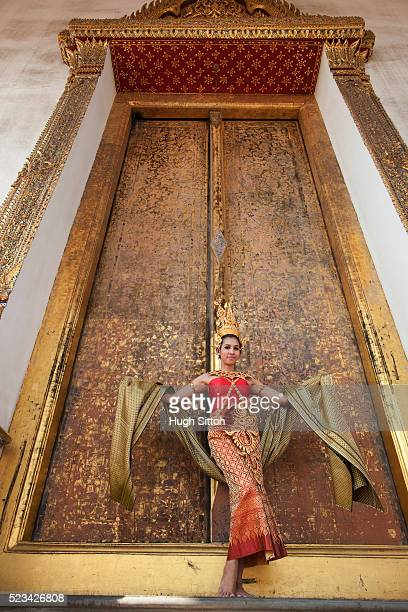 traditional thai dancer standing in front of decorated temple doors, bangkok, thailand - hugh sitton stock pictures, royalty-free photos & images