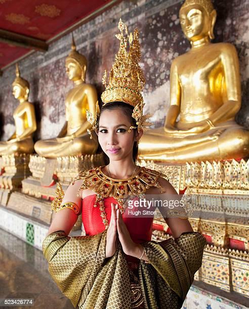 traditional thai dancer standing in front of seated buddhas, bangkok, thailand - hugh sitton bildbanksfoton och bilder