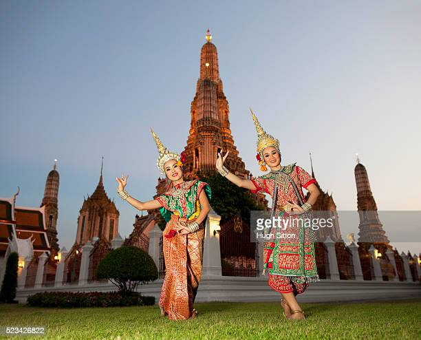 traditional thai dancers in front of the temple of arun, bangkok, thailand - hugh sitton stock pictures, royalty-free photos & images