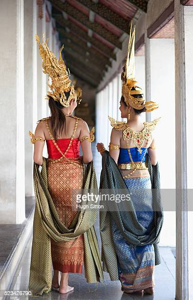 traditional thai dancers talking together in temple walkway, bangkok, thailand - hugh sitton stock-fotos und bilder