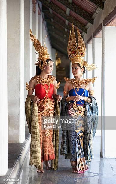 traditional thai dancers talking together in temple walkway, bangkok, thailand - hugh sitton fotografías e imágenes de stock
