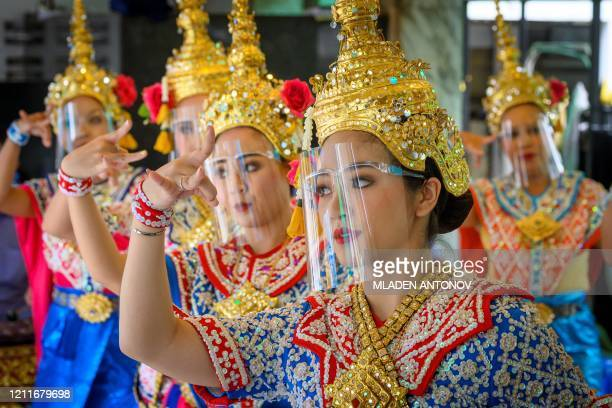 Traditional Thai dancers wearing protective face shields perform at the Erawan Shrine, which was reopened after the Thai government relaxed measures...