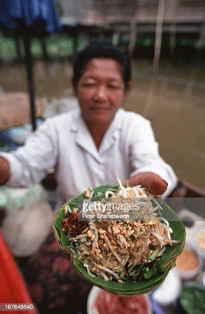 Traditional Thai food A dish of Phad Thai served in a bananaleaf bowl is held up by a food vendor sitting in her little boat on a Bangkok canal Small...