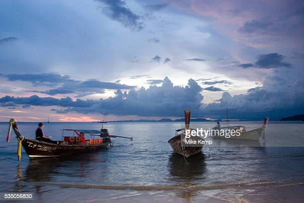 Traditional Thai longtail boats at sunset in the Andaman Sea at Railay West Bay Railay