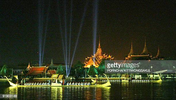 Traditional Thai royal barges parade along the Chao Phraya river as lights brighten up the sky above the Grand Palace during a cultural show put on...