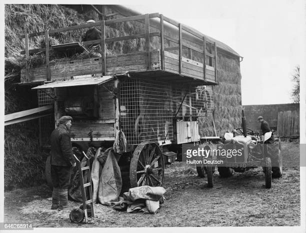 A traditional threshing machine still in use in 1965 It has been adapted to comply with safety standards a tractor rather than the traditional steam...