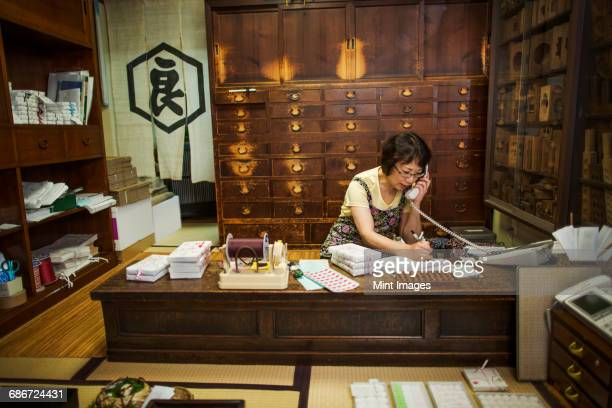 a traditional wagashi sweet shop. a woman working at a desk using a laptop and phone. - wagashi stock pictures, royalty-free photos & images
