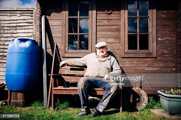 Traditional Wheelwright sitting on a bench outside his workshop