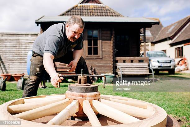 Traditional Wheelwright works on a large wooden cartwheel