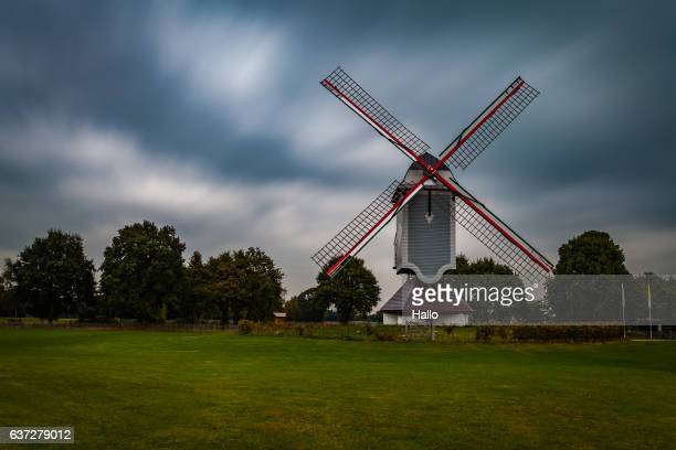 traditional wind mill in lomel, belgium, with clouds and grass field,long exposure. - traditional windmill stock photos and pictures