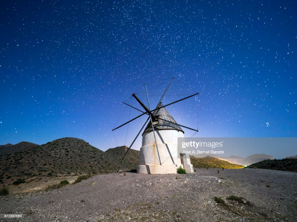 Traditional windmill among mountains in a sunny arid a night of blue sky with stars. Natural Park of Cabo de Gata - Nijar, in Almeria,  Andalucia, Spain. : Stock Photo