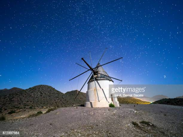Traditional windmill among mountains in a sunny arid a night of blue sky with stars. Natural Park of Cabo de Gata - Nijar, in Almeria,  Andalucia, Spain.