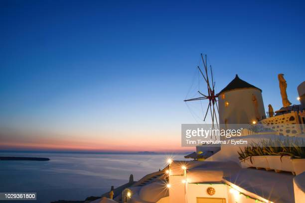 traditional windmill at santorini against blue sky during sunset - traditional windmill stock photos and pictures
