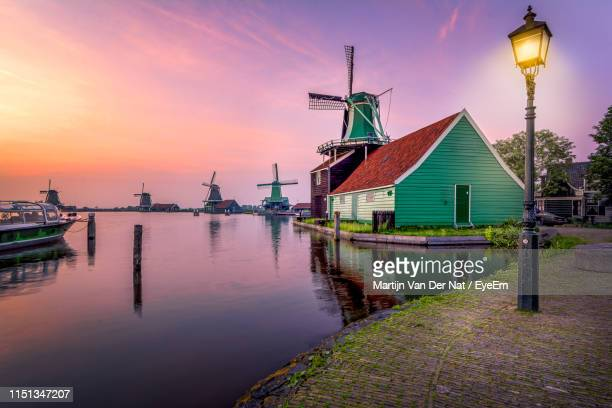 traditional windmill by building against sky during sunset - north holland stock pictures, royalty-free photos & images
