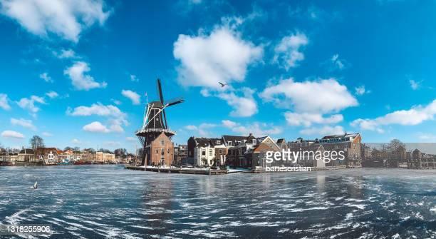 traditional windmill by building against sky - bortes imagens e fotografias de stock