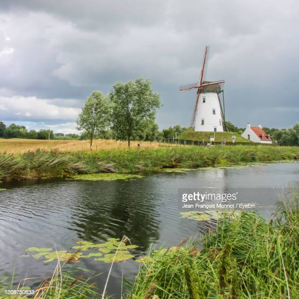 traditional windmill by lake against sky - damme stock pictures, royalty-free photos & images