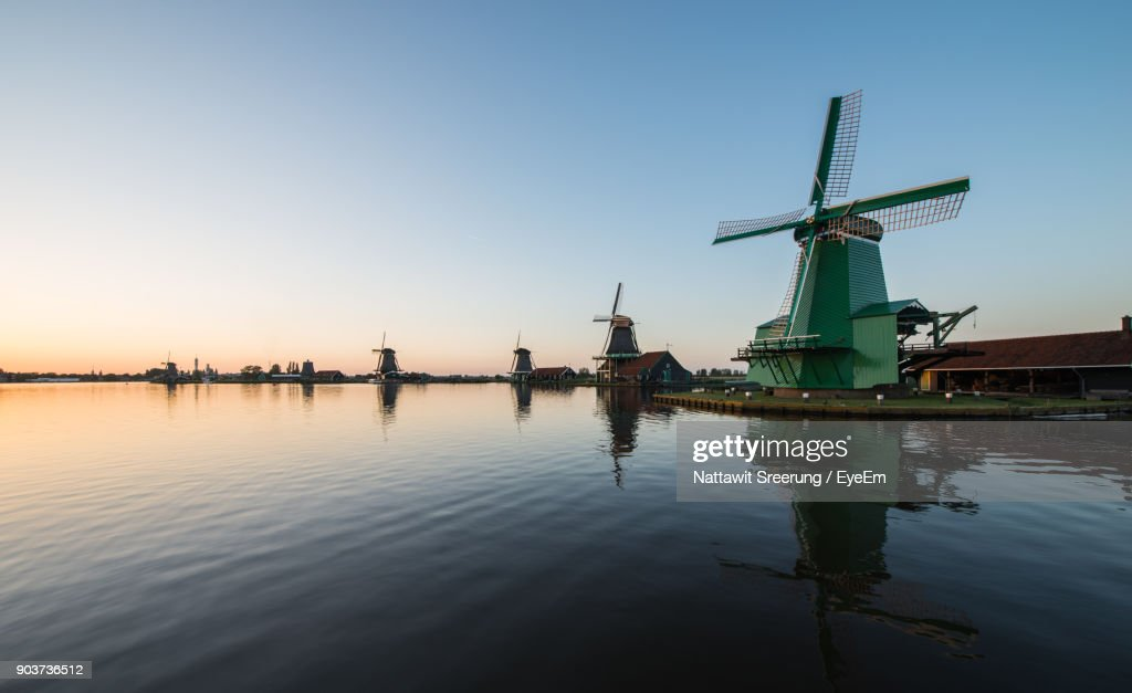 Traditional Windmill By River Against Sky : Stock Photo