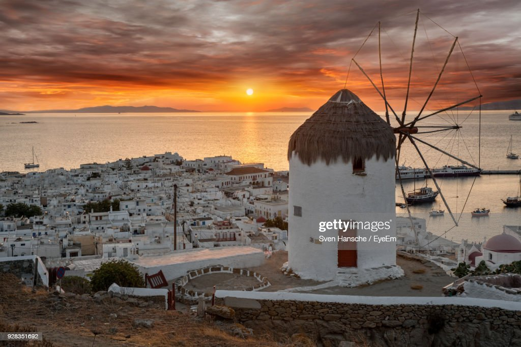 Traditional Windmill By Sea Against Sky During Sunset : Stock Photo