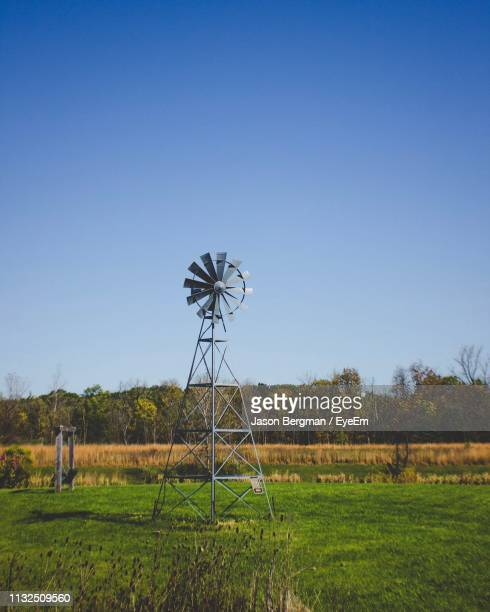 traditional windmill on field against clear blue sky - traditional windmill stock photos and pictures