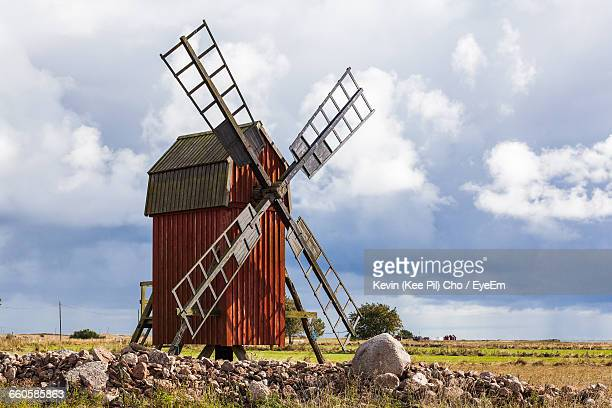 traditional windmill on field against cloudy sky - traditional windmill stock photos and pictures