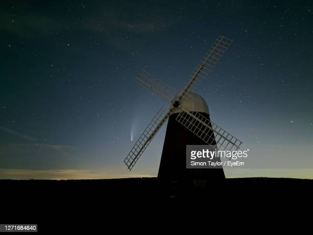 traditional windmill on field against sky at night with comet neowise - chichester stock pictures, royalty-free photos & images